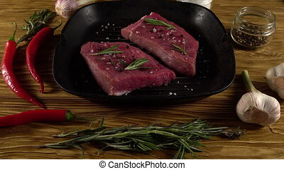 Beef fillet on a pan with pepper, rosemary and garlic.
