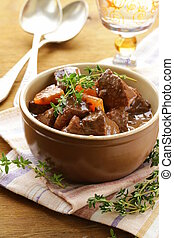 beef goulash (stew) with vegetables and herbs on a wooden...