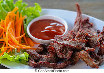 Beef in a white dish with vegetables and dipping sauce on a wooden table.