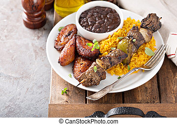 Beef kebab with rice, beans and fried plantains, south...