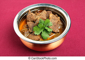 Beef korma in a stainless steel and copper serving bowl on a maroon tablecloth with a sprig of cilantro