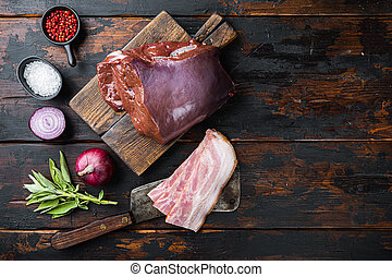 Beef liver with pancetta on wooden background, top view with copy space.