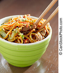beef lo mein in a bowl with chopsticks