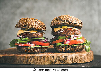 Beef meat cheeseburgers with barbeque sauce on board, close-up