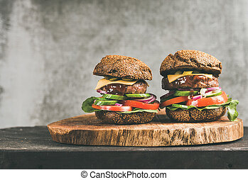 Beef meat cheeseburgers with barbeque sauce on board, copy space