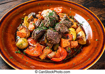 Beef meat stewed with vegetables on a plate. Dark wooden background. Top view