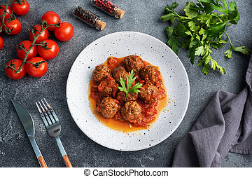 Beef meatballs stewed in tomato sauce on a plate. Dark concrete background.