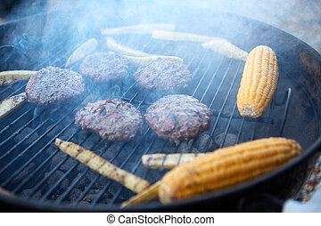 Beef patties and corn grilling on a barbecue