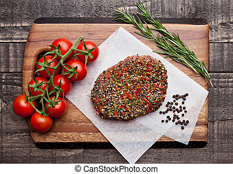 Beef raw steak with pepper and garlic on wood