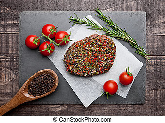 Beef raw steak with pepper and tomatoes on stone board