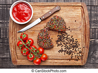 Beef raw steak with pepper and tomatoes on wooden board