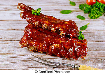 Beef ribs with barbecue sauce and fork on wooden board.