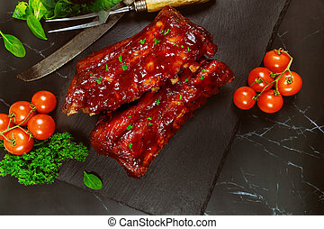 Beef ribs with barbecue sauce on black stone board.