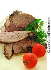 Beef roast cut on a wooden cutting board