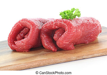 fresh raw beef rolls with parsley on a white background