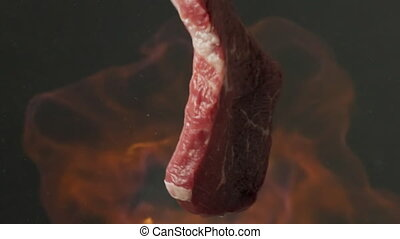 beef steak flies into a fiery flame on a gray background. slow motion