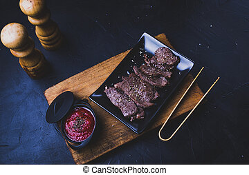 Beef steak cut into strips with tomato sauce on wood.
