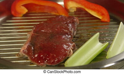 Beef steak grilled with vegetables on a frying pan