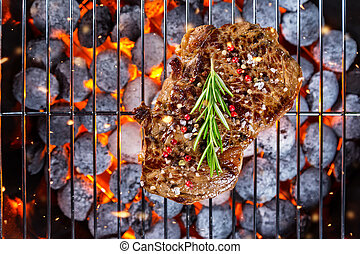 Beef steak on grill in fire, shot from above view