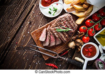 Beef steak on wooden table - Delicious beef steak on wooden ...