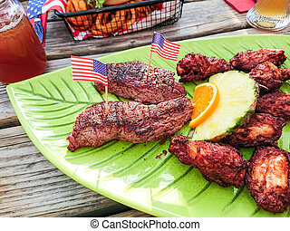 Beef steak with chicken wings and fruits