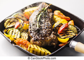 beef steak with grilled vegetables in skillet