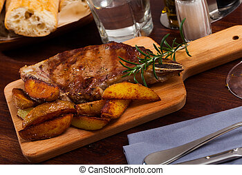 Beef steak with potatoes on a wooden board