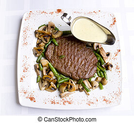 Beef steak with sauce, roasted green bean and mushrooms on...