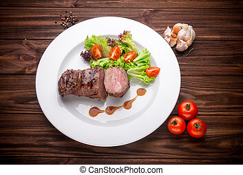 Beef steak with vegetables and seasoning on a wooden...