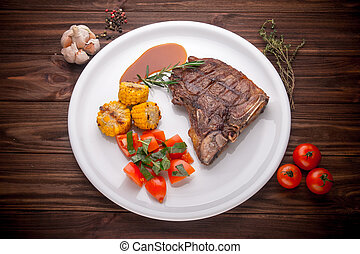 Beef steak with vegetables and seasoning on a wooden background