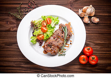Beef steak with vegetables and seasoning on wooden