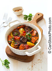 Beef stewed with vegetables on a white wooden background