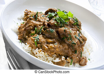 Beef stroganoff over white rice, garnished with parsley.
