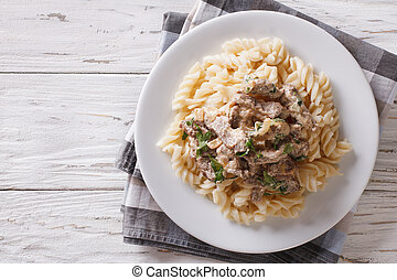 Delicious beef stroganoff with pasta fusilli on a plate on the table. Horizontal view from above