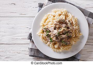 beef stroganoff with pasta fusilli . Horizontal top view -...