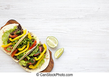 Beef tacos with salad and pepper.