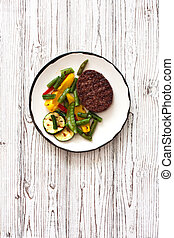 Beefsteak grilled with vegetables in white plate on a white wood background