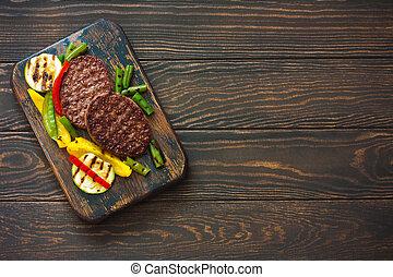 Beefsteak grilled with vegetables on a dark wood background
