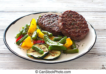 Beefsteaks grilled with vegetables in white plate