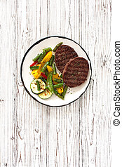 Beefsteaks grilled with vegetables in white plate on a white wood background