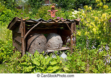 Beehives in the garden with scarecrow
