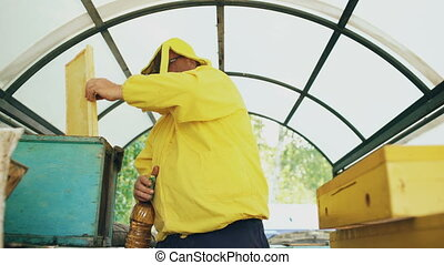 Beekeeper man watering wooden frame with sprayer and set up in beehive in apiary
