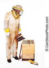 Beekeeper Smoking A Hive - an isolated beekeeper in...