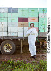Beekeeper Standing Against Truck Loaded With Crates