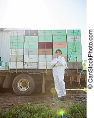 Beekeeper Standing Against Truck Loaded With Honeycomb Crates