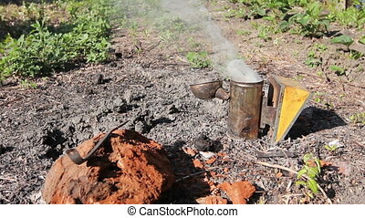 Beekeeper's smoking pot with smoke, open on the ground -...