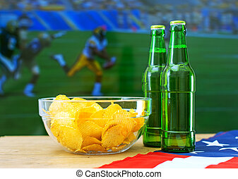 Beer and chips in front of TV with American football match.