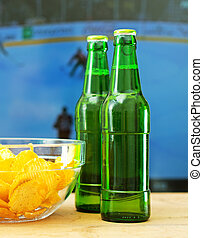 Beer and chips in front of TV with hockey match.