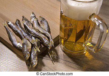 Beer and dried fish on wooden table.