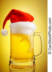 Beer and hat of Santa Claus on a yellow background